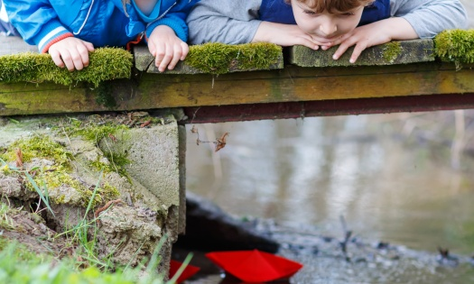 Two little brothers playing together with colorful paper boats by a river on spring or autumn day. Creative leisure with kids.